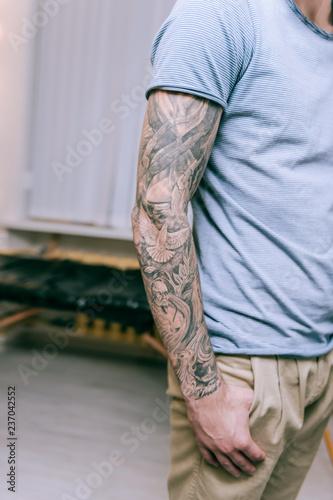 Dysponowany młody człowiek ma całą rękę faszerującą z tatuażem