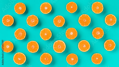 Fruit pattern of fresh mandarin slices on blue background. Flat lay, top view. Pop art design, creative summer concept. Half of citrus in minimal style. Tangerine. - 237045597