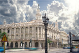 The Grand Theatre in the central of Havana in Cuba with classic american cars and tourists rushing by.
