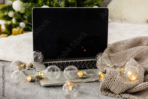 Foto Murales Image of open laptop with white screen on wooden table in front of christmas tree background. For mockup