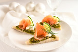 festive canapes with smoked salmon, pesto, cucumber and dill garnish, white table cloth and christmas decoration, copy space - 237050531
