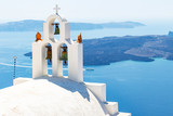 Views of the volcanic island Tholos along the clock tower of a chapel in Fira, Santorini, Greece - 237054904