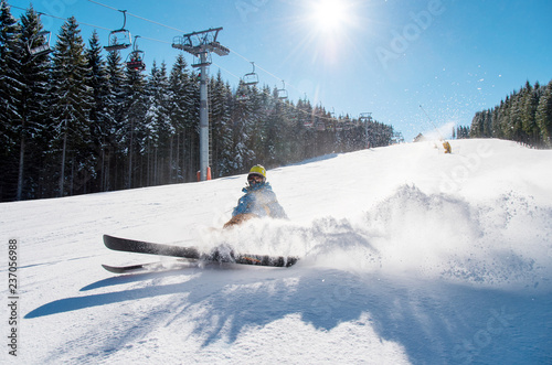 Skier falling on the slope on fresh powder snow at winter resort. Blue sky, sun and winter forest on the background copyspace adventure extreme adrenaline active lifestyle concept - 237056988