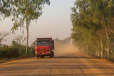 Fototapeta Sawanna - Truck speeding along dirt road across savannah and lifting large amount of dust. © anzebizjan