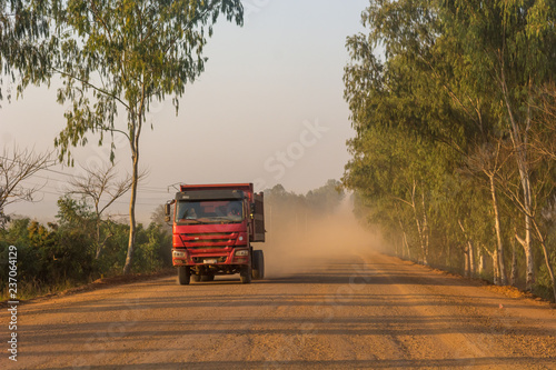 Truck speeding along dirt road across savannah and lifting large amount of dust. © anzebizjan