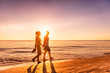 Leinwanddruck Bild - Couple walking on beach at sunset silhouettes - Romantic summer travel holidays in Caribbean destination