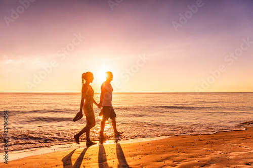 Leinwanddruck Bild Couple walking on beach at sunset silhouettes - Romantic summer travel holidays in Caribbean destination