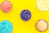 Spa salt background. Colorful spa salt in bowls on yellow background top view. Yellow, turquoise, pink, purple spa salt