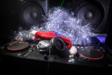 Dj mixer with headphones on dark nightclub background with Christmas tree New Year Eve. Close up view of New Year elements on a Dj table. Holiday party concept. - 237069980