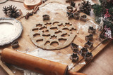 Christmas gingerbread cookies dough with metal cutters on rustic table with wooden rolling pin, cinnamon ,anise, cones, christmas decorations. Atmospheric stylish image, winter holidays