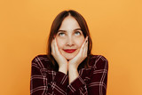 Woman portrait. Emotions. Girl is looking upwards and smiling, hands on her cheeks, on an orange background - 237074727