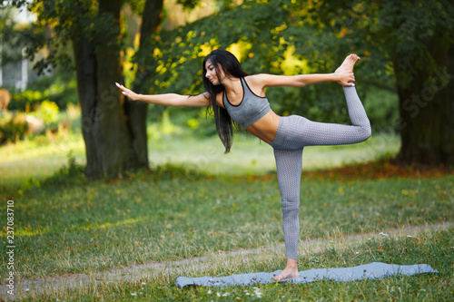 Naklejka Young beautiful woman practicing yoga in the green park. Wellness concept. Calmness and relax, woman happiness.