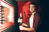 handsome man in headphones is going to record his song in the studio with red wall. close up photo. making a record for hit