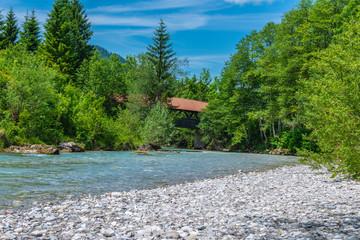 Wildbach in den Bergen mit einer hölzernen Brücke überdacht Hinterstein Hindelang Allgäu