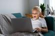 Leinwandbild Motiv Young boy watching videos on his laptop
