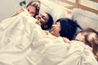 Group of diverse women lying on bed together under the blanket