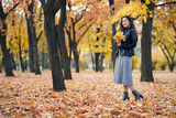 Pretty woman is posing with bunch of maple's leaves in autumn park. She's closing eyes and dreaming. Beautiful landscape at fall season. - 237113914