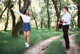 young couple walking in the forest and playing guitar, summer nature, bright sunlight, shadows and green leaves, romantic feelings - 237113932