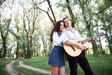 young couple walking in the forest and playing guitar, summer nature, bright sunlight, shadows and green leaves, romantic feelings - 237113951