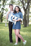 young couple posing with flags in the forest, summer nature, romantic feelings - 237113979