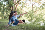 young couple sitting on the grass in the forest and looking on sunset, summer nature, bright sunlight, shadows and green leaves, romantic feelings - 237113989
