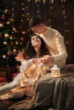 young couple is in christmas lights and decoration, dressed in white, fir tree on dark wooden background, winter holiday concept - 237114101