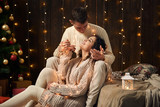 young couple is in christmas lights and decoration, dressed in white, fir tree on dark wooden background, winter holiday concept - 237114147
