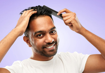 grooming, hairstyling and people concept - smiling young indian man brushing hair with comb over ultra violet background