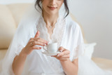 the bride is drinking coffee, bride holds a cup of coffee, bride in a white coat, morning of the bride, wedding day - 237125500