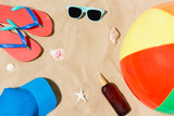 vacation and summer holidays concept - cap, flip flops, sunglasses, beach ball and sunscreen oil with seashells on sand