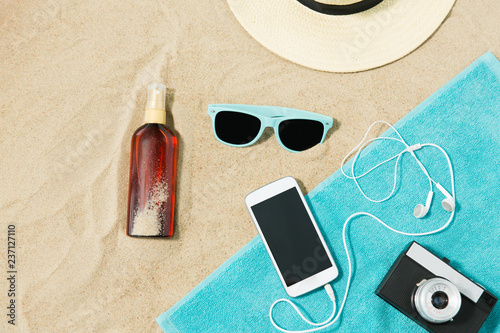 vacation and summer holidays concept - smartphone with earphones and film camera on towel, straw hat, sunglasses and bottle of sunscreen oil on beach sand - 237127110