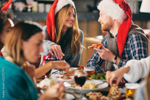 Friends having dinner at home at Christmas eve. Winter holidays concept. - 237127931