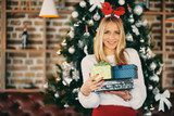 Young woman standing and holding gifts in front of Christmas tree. Christmas holidays concept.