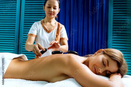 Thai therapist doing massage with hot stones. - 237129313