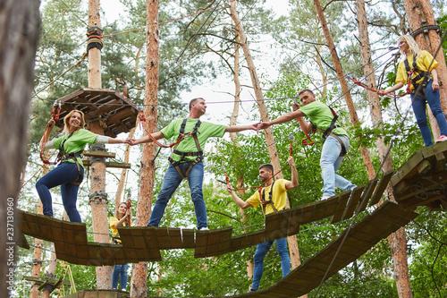 Leinwanddruck Bild Gruppe macht Teamwork im Hochseilgarten