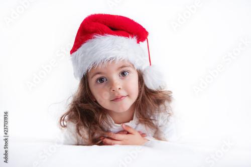 Leinwandbild Motiv Christmas time, little girl in Santa Claus hat smilling