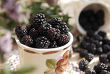 Fresh blackberries scattered from the cup on a wooden table.