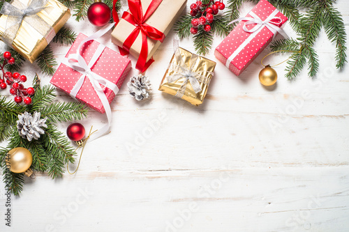Red and Gold present box and decorations on white wooden backgro