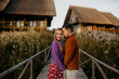 Happy couple posing in front of wooden house