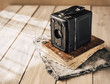Vintage analogue film camera on a wooden table, old book, clothl. Retro photo. Copy space