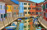 Burano island picturesque street with small colorful houses, smal water canal with beautiful reflections and fishermans boats, Venice Italy