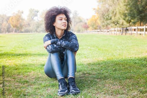 Sporty Afro Amerykańska młoda kobieta Relaksuje Na Zielonej trawie Przy parkiem