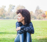 Sporty Afro American Young Woman Relax On Green Grass At Park