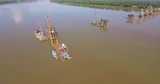 aerial panning shot of bridges foundations and  barges mounted cranes in river  - 237175165