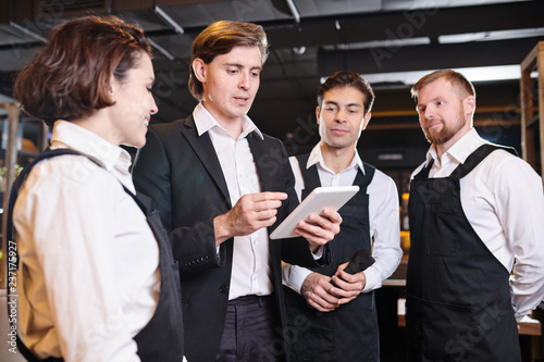 Leinwanddruck Bild Briefing of waiters: serious confident handsome young manager using tablet and giving tasks to waiting staff while they preparing for banquet
