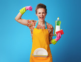 housewife with sponge and dish soap showing biceps on blue