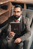 Dark-haired bearded man holding the Holy Bible