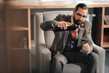 Man wearing nice expensive hand watch pouring wine into glass