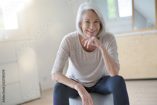 Leinwanddruck Bild  Attractive elderly woman exercising at home with swiss ball