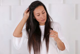 Hair care concept. Woman Checking Her Hair for Split Ends. Damaged long hair